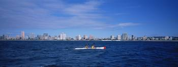 Surf ski in water with buildings in the backgroun