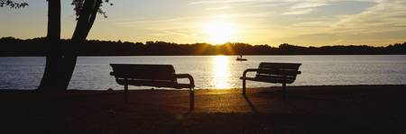 Silhouette of two benches at the lakeside