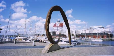 Sculpture at a harbor with boats in the backgroun