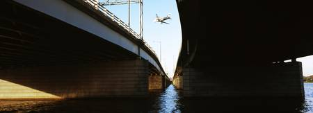 Airplane viewed through two highway bridges U.S.