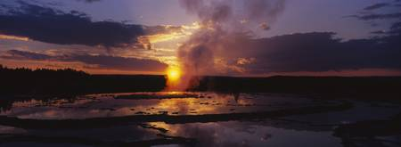 Steam emitting from a natural geyser at sunset