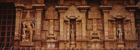 Three statues of gods carved on the wall of a tem