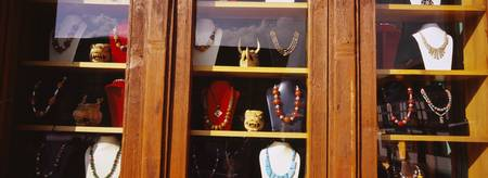 Close-up of necklaces in a window