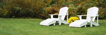White Adirondack Chairs On A Lawn