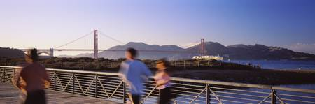 Rear View Of Three People Jogging On A Bridge