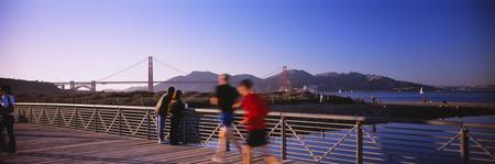 Five People Jogging On A Bridge