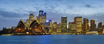 Opera house and buildings lit up at dusk Sydney O