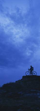 Silhouette of a mountain biker standing on a clif