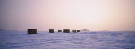 Ice fishing shacks on a frozen lake