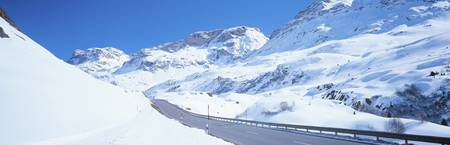 Snow covered mountains on both sides of a road