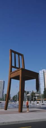 Woman standing under a sculpture of large broken