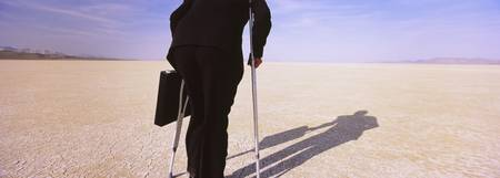 Businessman walking in a desert on crutches with