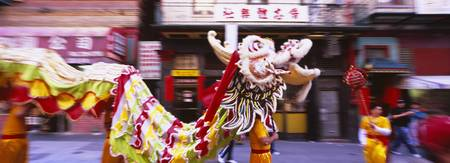 Group of people performing dragon dancing on a ro