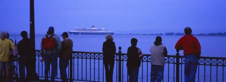 Rear view of tourists standing on a pier and look