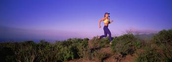 Side profile of a young woman running on a hill