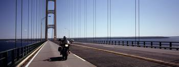 Person riding a motorcycle on a bridge Mackinac B