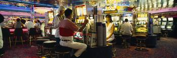 Group of people playing on slot machines in a cas