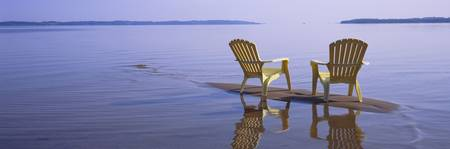 Reflection of two adirondack chairs in a lake
