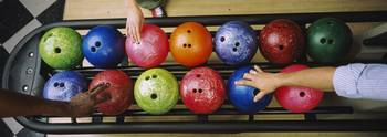 Three peoples hands choosing bowling balls