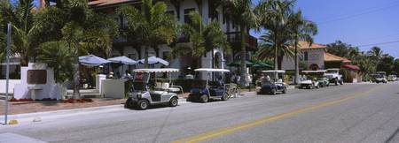 Golf carts and cars parked on a street