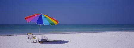 Beach umbrella and a folding chair on the beach