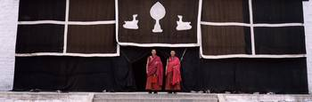 Two monks standing in front of religious symbols