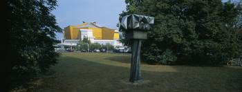 Sculpture in a lawn with a concert hall in the ba