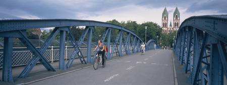 Woman riding a bicycle on a bridge with a church