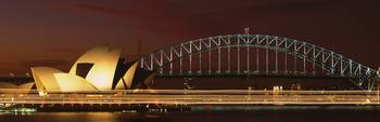 Opera house lit up at night with light streaks