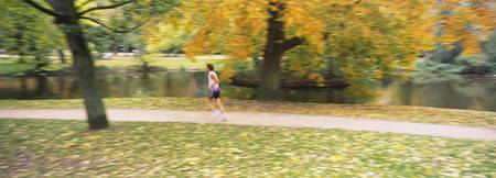 Side profile of a person jogging in a park