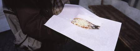 Person holding a raw herring with chopped onion f