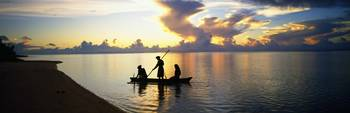 Three people in canoe at sunset