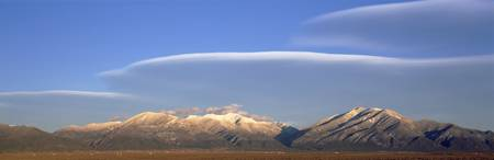 Lenticular clouds over a mountain range Taos Moun