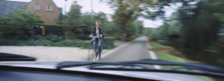 Woman riding a bicycle viewed through a windshiel