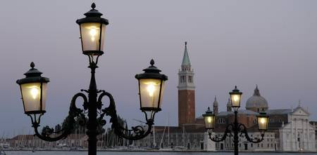 Lampposts lit up at dusk with building in the bac