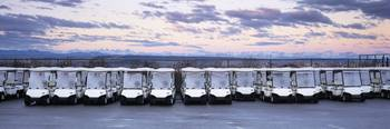Golf carts parked in a parking lot