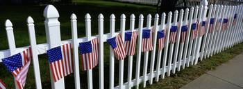 American flags hanging on a picket fence