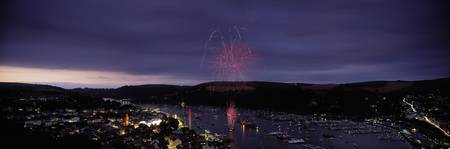 Fireworks display at night over a town during reg