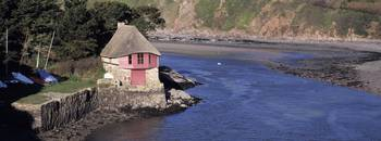 Thatched roofed boathouse on the coast Bantham So