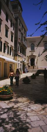 Two women walking in front of a courtyard in Corf