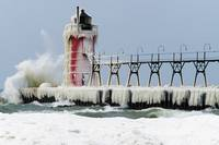 Wave crashing on snow-covered South Pier lighthou