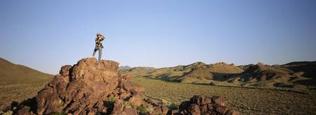 Rear view of a man standing on the top of a rock