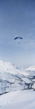 Person parasailing over a snow covered mountain