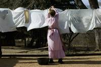 Rear view of a woman drying clothes on a clothesl