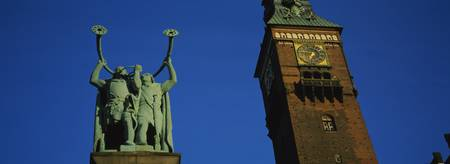 Low angle view of a statue and a clock tower