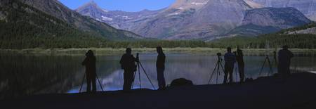 Photographers standing at a lakeside