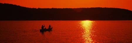 Tourists canoeing in a lake at sunset