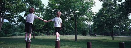 Rear view of two boys standing on wooden posts an