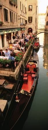 Gondolas moored outside of a cafe