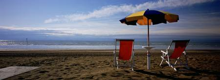 Two empty chairs under a beach umbrella